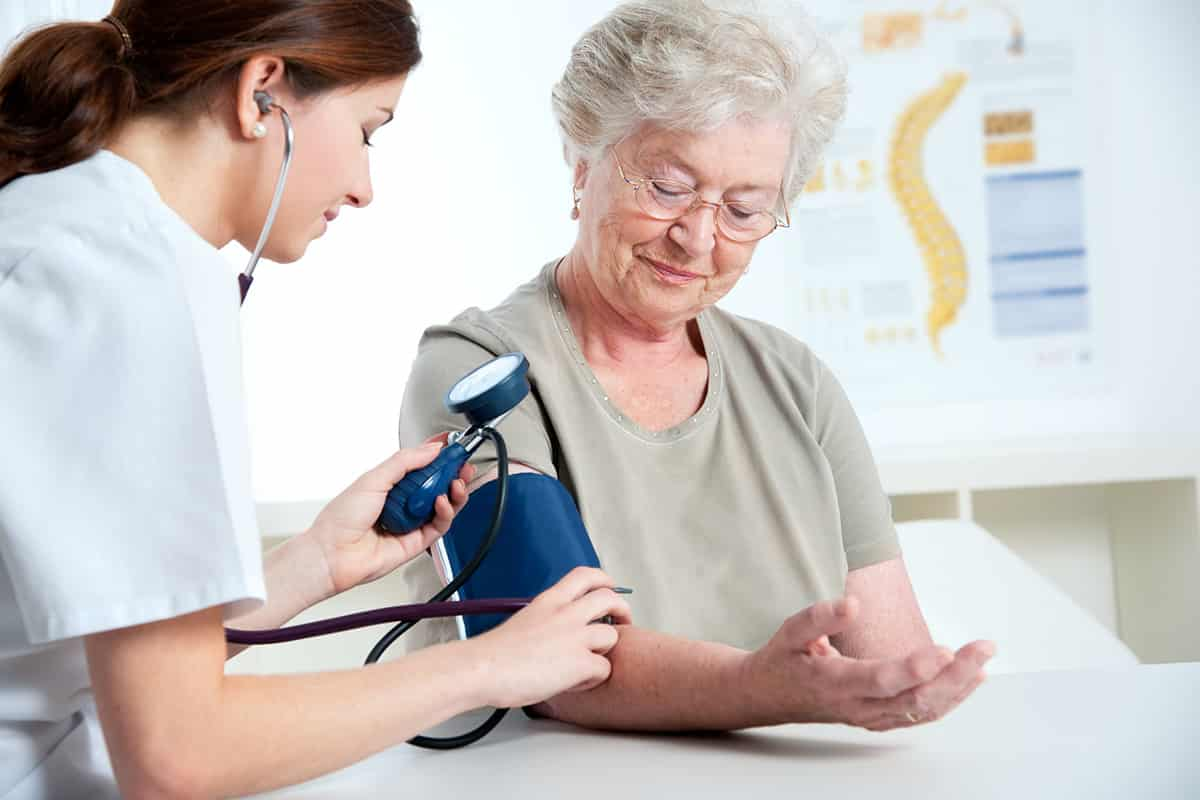 Medical assistant measuring blood pressure